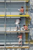 stock photo of mortar-joint  - Four plasterers working outside on scaffolding - JPG
