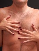 Woman with deep red fingernails embracing man's hairy torso