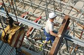 Construction worker unloading steel beam on scaffolding