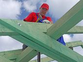 foto of purlin  - Roofer driving a nail into house rafter beam - JPG