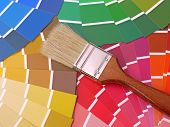 Paint brush on array of different paint color swatches