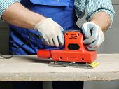 Closeup of carpenters hands sanding plank using power finishing sander