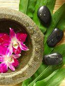 Orquídeas roxas em água perfumada, pedras de terapia em folhas verdes