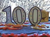 stock photo of centenarian  - a colorful birthday cake with candles shaped like the number 100 - JPG