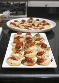 petite pastries with crab, onion, tomato baked in oven