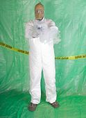 Man in Hazmat clothing in temporary green plastic decontamination chamber wearing a gas mask and carrying toxic chemical that is exuding gaseous vapor