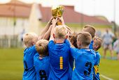 Young Soccer Players Holding Trophy. Boys Celebrating Soccer Football Championship. Winning Team Of  poster