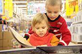 Постер, плакат: Двое детей посмотреть книгу в магазине