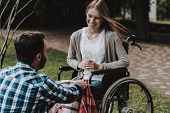Girl On Wheelchairs With Man On Picnic In Park. Disabled Young Woman. Woman On Wheelchair. Relaxing  poster