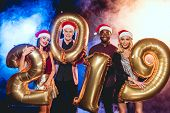 Glamorous Friends In Santa Hats Holding 2019 New Year Golden Balloons On Black With Smoke And Backli poster