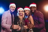 Multicultural Glamorous Friends In Santa Hats Clinking With Champagne Glasses On New Year Party poster