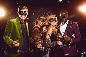 Glamorous Multiethnic Friends In Carnival Masks Holding Champagne Glasses And Celebrating New Year O poster