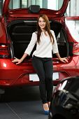 Beautiful Girl Is Sitting On The Car Trunk. She Is Looking For New Car In The Car Dealership. Car Is poster