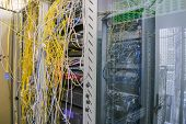 Racks With Servers Are Located In The Server Room. Messy Internet Wires Have A Connection To Compute poster