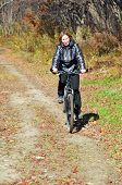Young woman cycling in the fall forest