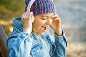 Girl Listens To Music In Headphones. Smiling Girl Relaxing, Music A Smartphone And Headphones. Outdo poster