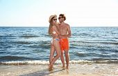 Happy Young Couple In Beachwear Spending Time Together At Seashore On Sunny Day poster