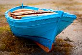 Old Blue Wooden Boat On Grassy Sand