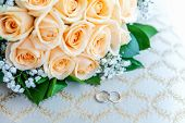 Beautiful Wedding Rings Lie On Light Surface Against Background Of Bouquet Of Flowers. Declaration O poster