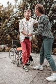 Reliable Social Worker Helping Her Disabled Patient To Stand Up poster
