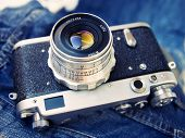 film rangefinder camera on jeans background (shallow focus on lens).