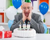 surprised senior man looking at birthday cake, so soon these years