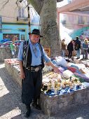 Street vendor dressed as gaucho offers souvenirs in La Boca area of Buenos Aires