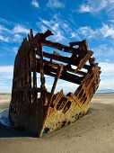 Rusty Wreckage Of A Ship On A Beach On The Oregon Coast Usa