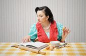 stock photo of stereotype  - Young woman looking at a Recipe for a cake - JPG