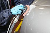 stock photo of buff  - Painter polishes a car body component - JPG