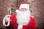 stock photo of sparkling wine  - Santa Claus with a glass of sparkling wine champagne under snowfall near a Christmas tree - JPG