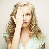 young woman covering her eyes with her hands. Studio shot agains