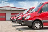 stock photo of in front  - Row of generic red delivery and service cars in front of a factory and warehouse distribution plant - JPG