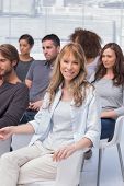 Woman smiling at camera in group therapy all sitting on chairs