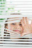 Niño feliz mirando a través de las persianas de la ventana
