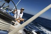 stock photo of pulley  - Sailor at the helm of a yacht in the ocean against blue sky - JPG