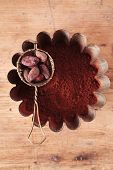 cocoa beans in sieve with cocoa powder in tinware on wood background