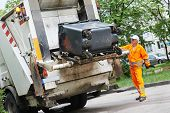 stock photo of dump  - Worker of municipal recycling garbage collector truck loading waste and trash bin - JPG