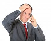 Attractive businessman getting bad news. All on white background.