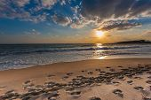 image of orbs  - Beautiful tranquil cloudy sunset over a deserted beach with the fiery orange orb of the sun low in the sky casting a path across the water of the ocean lighting up the indented footprints on the sand - JPG