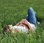 Attractive young woman taking a nap on green meadow.
