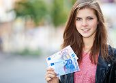 Attractive young woman in the city holding 70 euro.