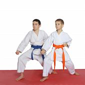 Two athletes with orange belt and blue belt stand in rack