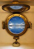 view on blue sea through nautical porthole