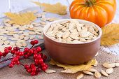 Pumpkin seeds in bowl with pumpkin on table close up