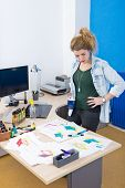 Creative designer standing behind her desk, overlooking various designs and concepts during for the