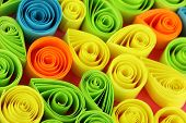 Colorful quilling on pink background close-up