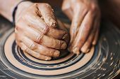stock photo of molding clay  - Potter Hands Making In Clay On Pottery Wheel.