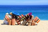 Mexican vendor with woven bags on the beach.