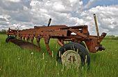 Vintage plow in field of long grass